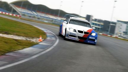 BMW 320i WTCC in the corner on a racetrack